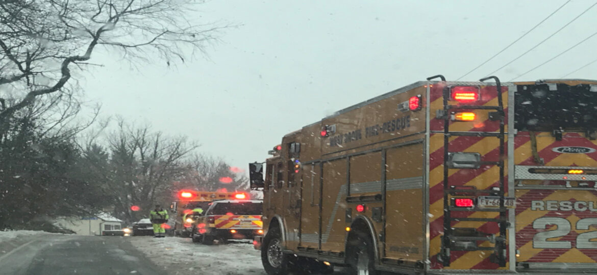 Snowy road windshield view. Fire truck and ambulance on road with lights on