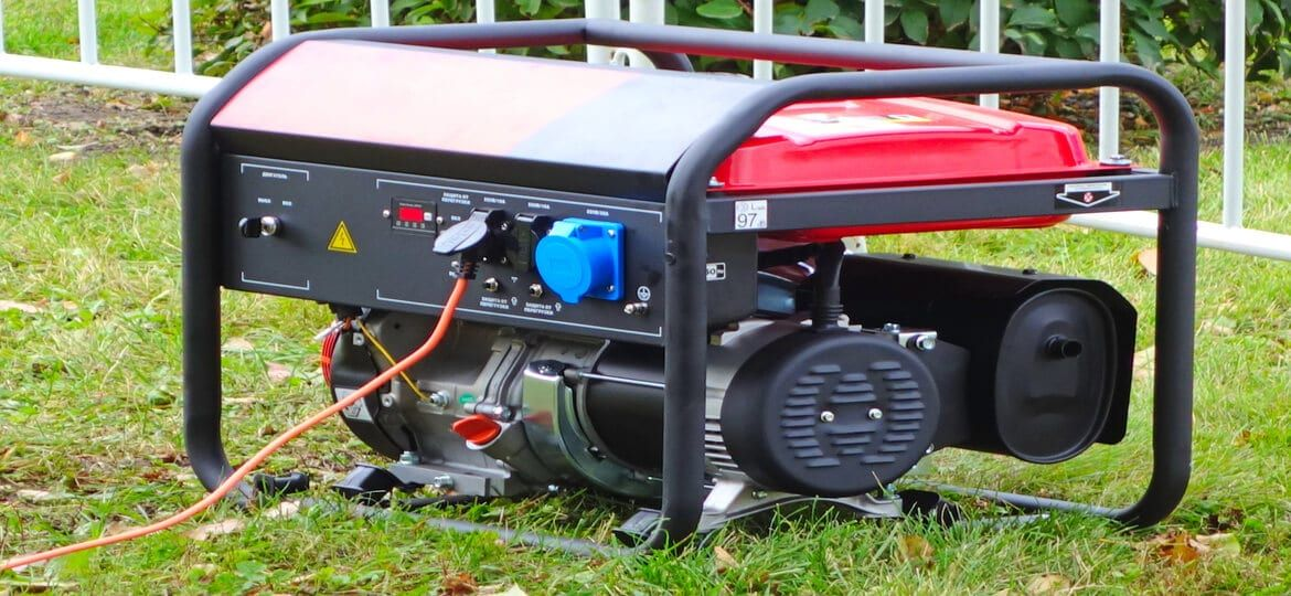 portable generator outside on green grass with cord attached - Mintz & Geftic